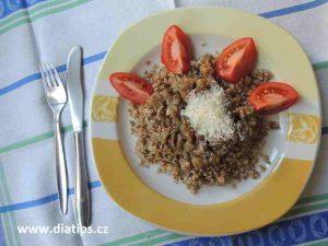 houbový bulgur ozdobený rajčetem na talířu